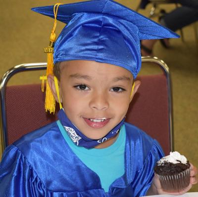 Little Learners graduate eating a cupcake